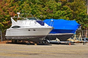2 boats dry docked 1 with shrink wrap 1 with out. preparing Watercraft Transport