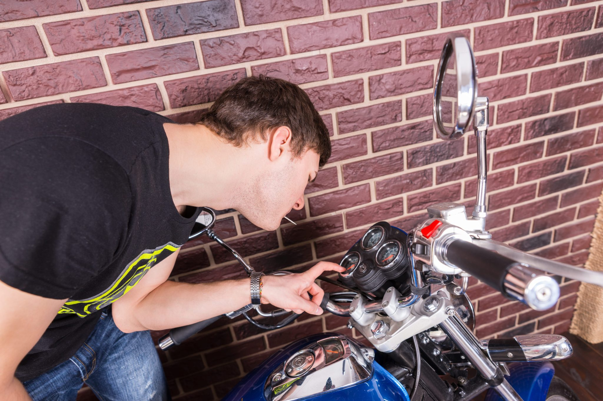 Preparing your motorcycle for transport-Man inspecting gauges on a motorcycle-Motorcycle Shipping