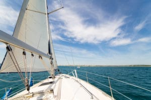 Yatch sail and desk on blue sky and sea background